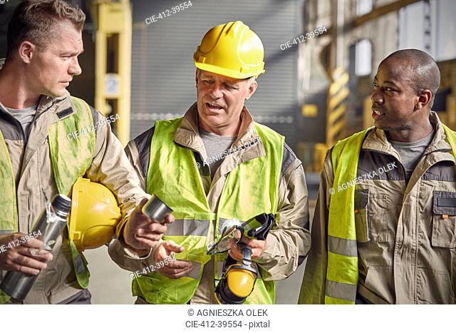 Steelworkers with insulated drink container taking coffee break in steel mill