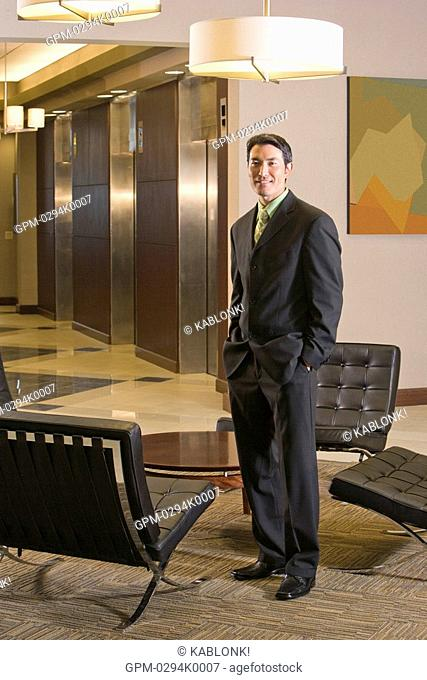 Portrait of Asian businessman standing in modern lobby