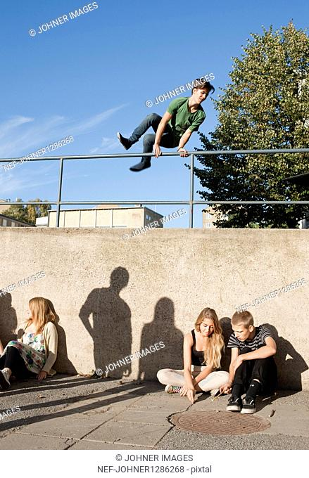 Teenage boy jumping over railings while other teenagers are sitting against wall