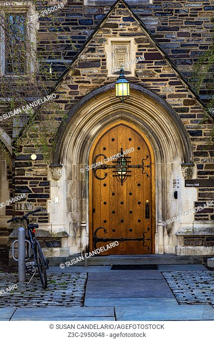 Princeton University Henry Hall - Exterior view of of window, lamp, wooden door, arch, stonework and a tudents bicycle ay the middle entry of the Henry Hall...
