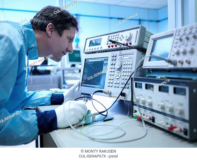 Worker checking electronics in clean room laboratory