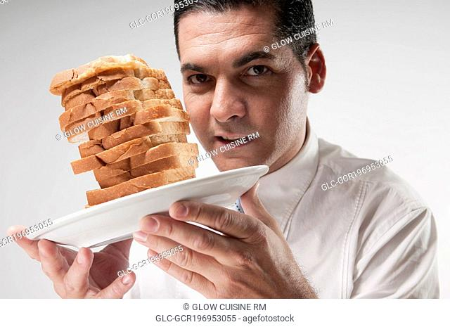 Portrait of a businessman holding sliced breads on a plate