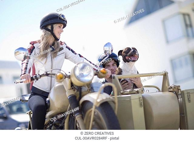 Couple with dog riding a motorbike