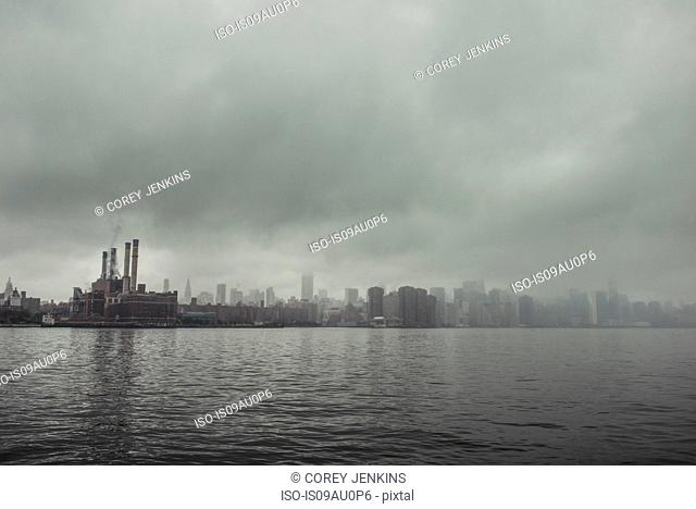 Foggy view of waterfront power station and chimney stacks, New York, USA