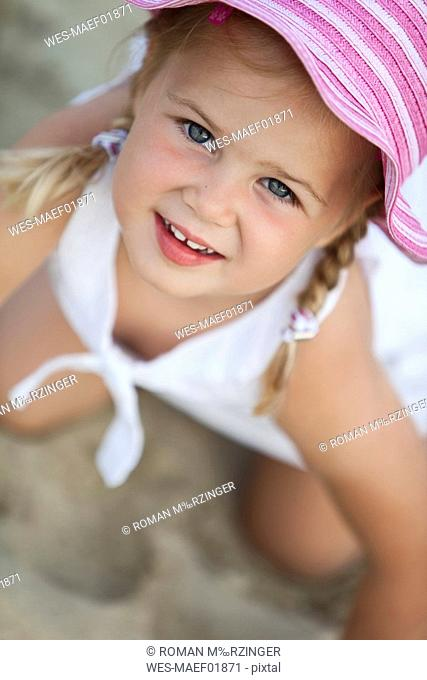 Germany, Girl 4-5 wearing summer hat, smiling, portrait, close-up