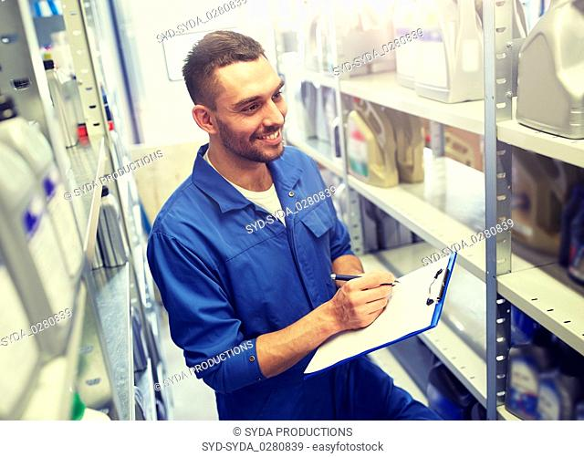 smiling auto mechanic with clipboard at car shop