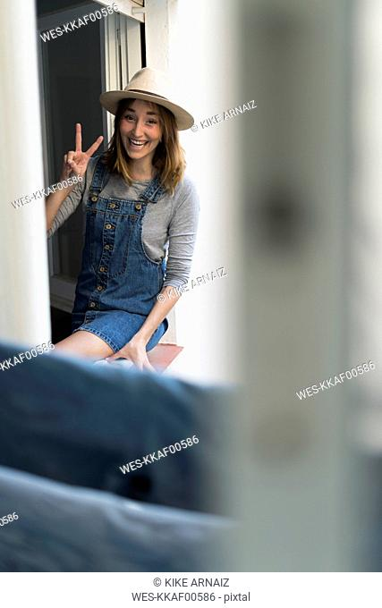 Happy young woman sitting in window frame making victory sign