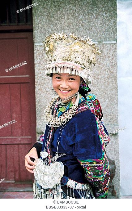 Portrait of cheerful young woman wearing Miao minority dress, Xijiang Miao Village, Kaili City, Guizhou Province of People's Republic of China