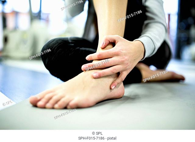 MODEL RELEASED. Young woman massaging ankle in gym