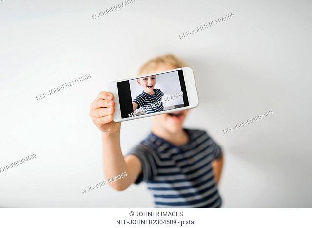 Cute boy taking selfie