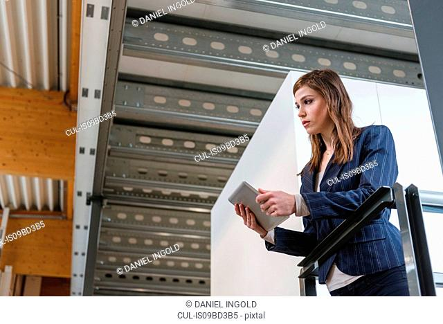 Young woman standing in factory, leaning on railing, using digital tablet, low angle view