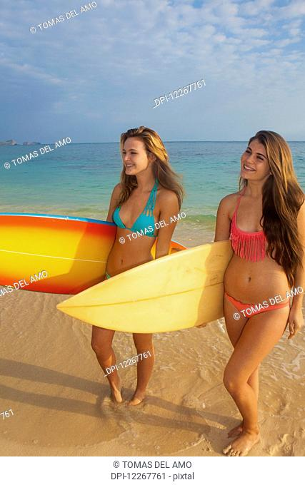 Teenage sisters at the beach with their surfboards; Kailua, Island of Hawaii, Hawaii, United States of America