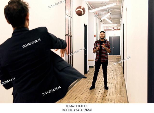 Men in corridor throwing rugby ball