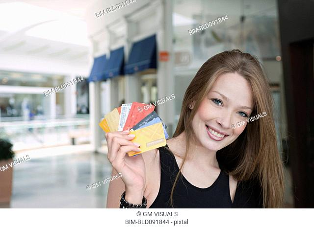 Hispanic woman holding credit cards in mall