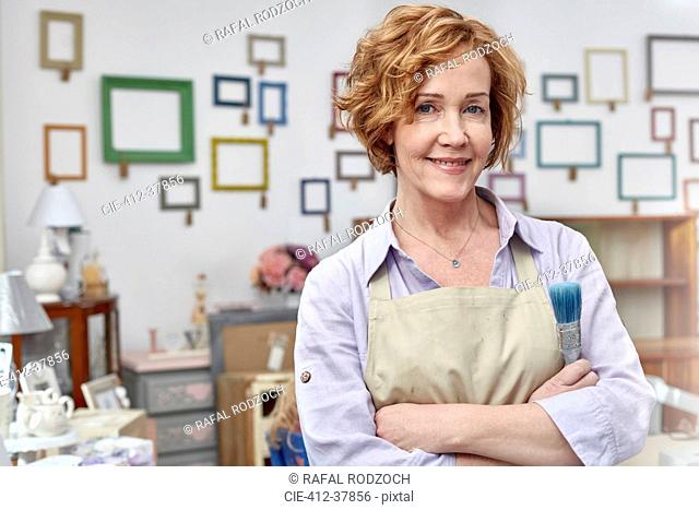 Portrait smiling mature female artist in art shop with picture frames