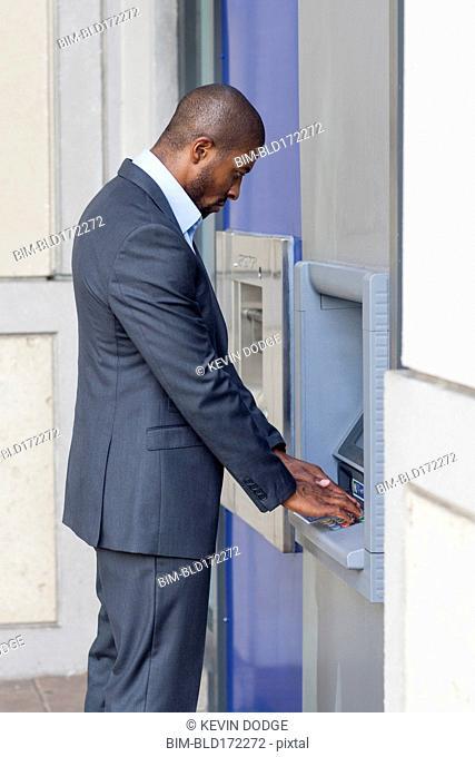 Black businessman using ATM in city