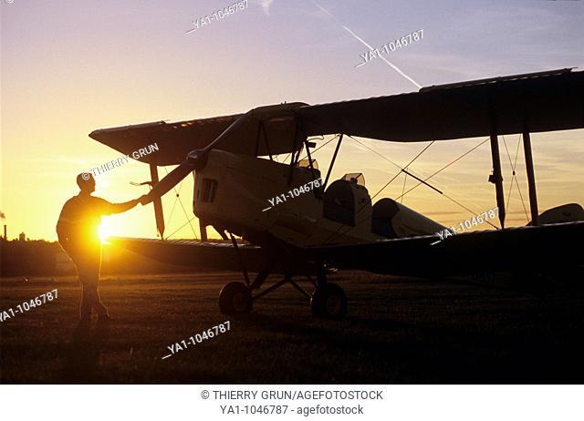 Pilot near an old trainer biplane De Havilland DH 82a Tiger Moth on sunset