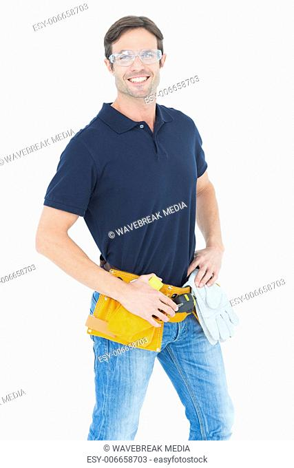 Confident man wearing tool belt over white background