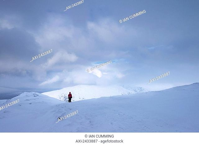 Woman walking up Beinn Dorain in snowy, winter conditions, near Bridge of Orchy; Argyll and Bute, Scotland