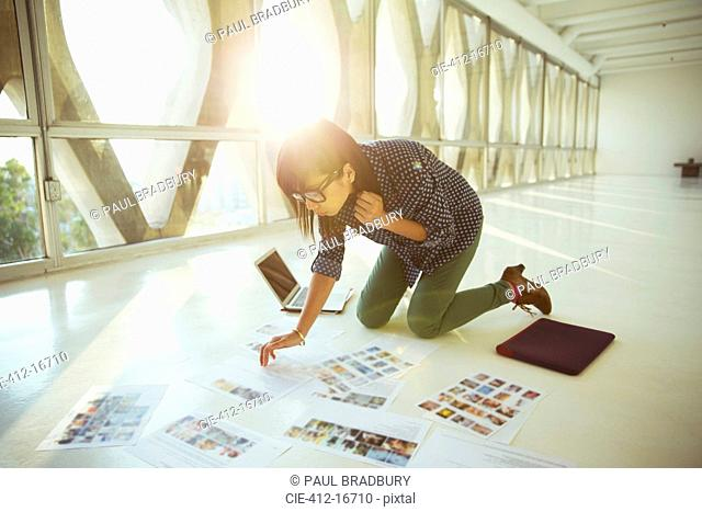 Creative businesswoman reviewing photography proofs on office floor