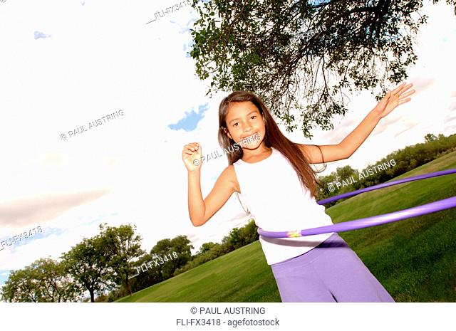Girl Twirling Hula Hoop in Park