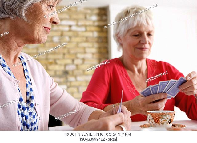 Senior women playing cards at home