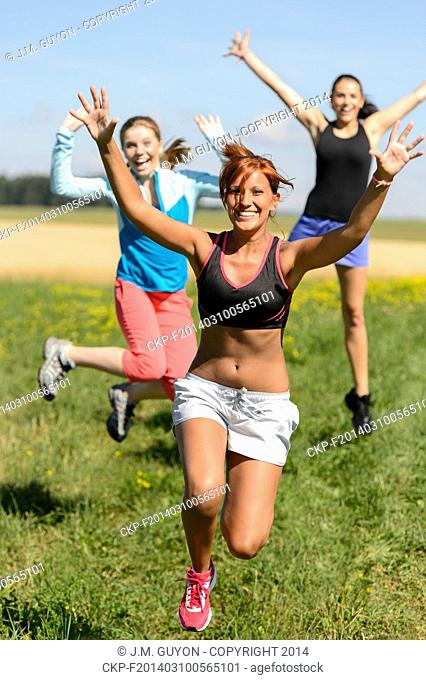 Cheerful friends jumping enjoy summer sport running sunny meadow