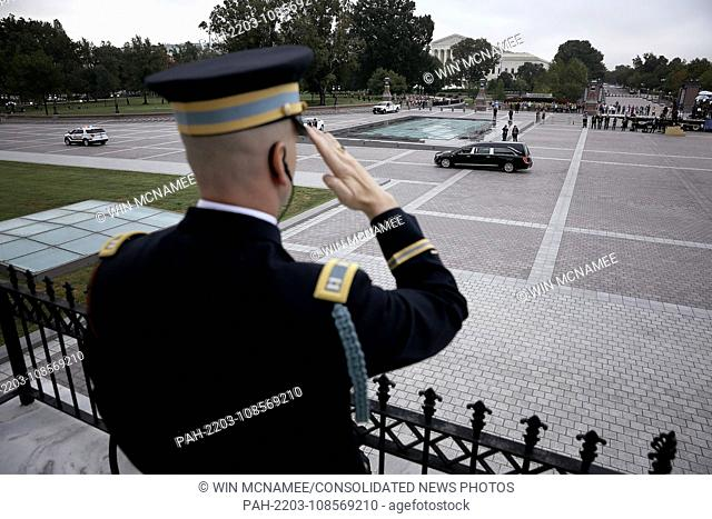 WASHINGTON, DC - SEPTEMBER 01: A member of a military honor guard team salutes as a hearse carrying the casket of the late-Sen