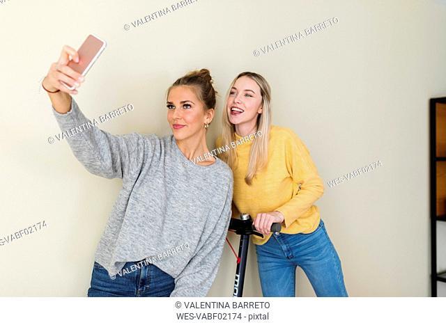 Girlfriends taking smartphone selfies