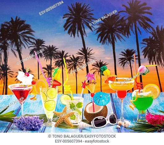 Colorful many tropical Cocktails in tropical blue wood Palm tree sunset with coconut mojito pepermint margarita