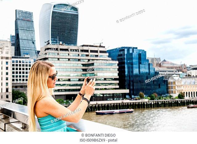 Female tourist standing on London Bridge, photographing view