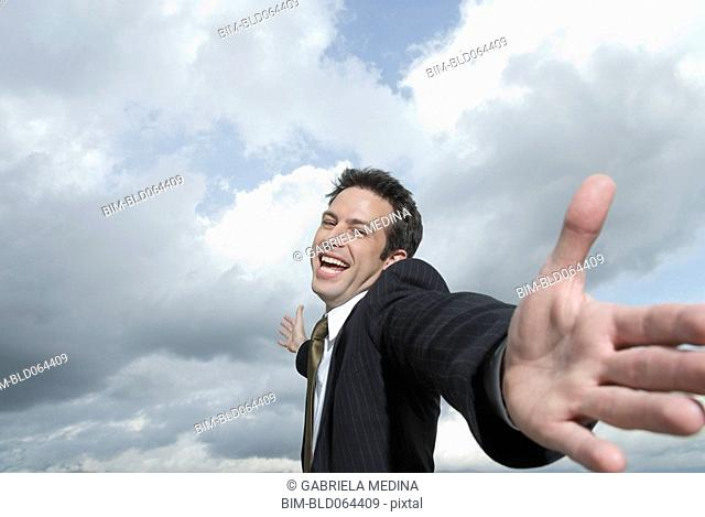 Hispanic businessman with arms outstretched