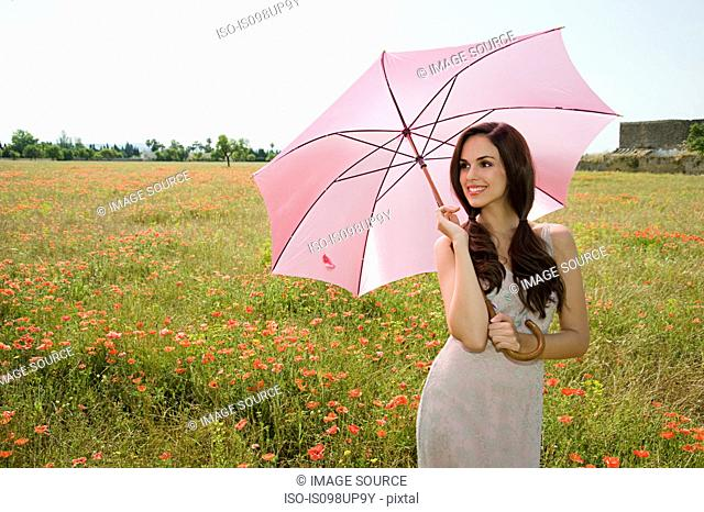 Young woman in poppy field with pink parasol