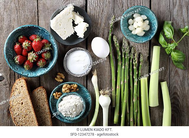 Ingredients for a strawberry salad with asparagus, bread, spring onions and feta