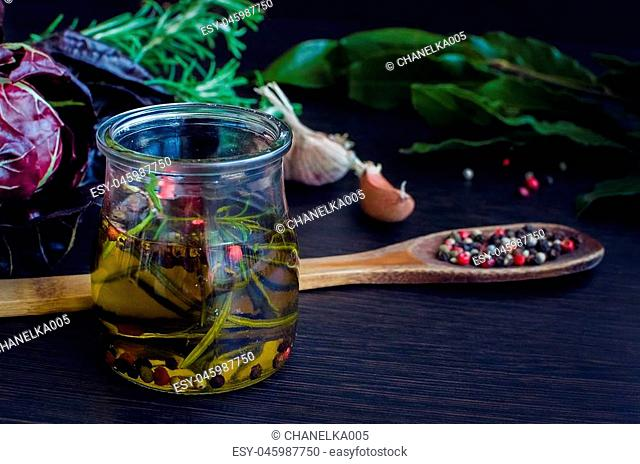 Olive oil with rosemary, garlic, chicory and pepper. Olive oil in bottle with rosemary and spices on a brown table. Olive oil flavored with spices and other...
