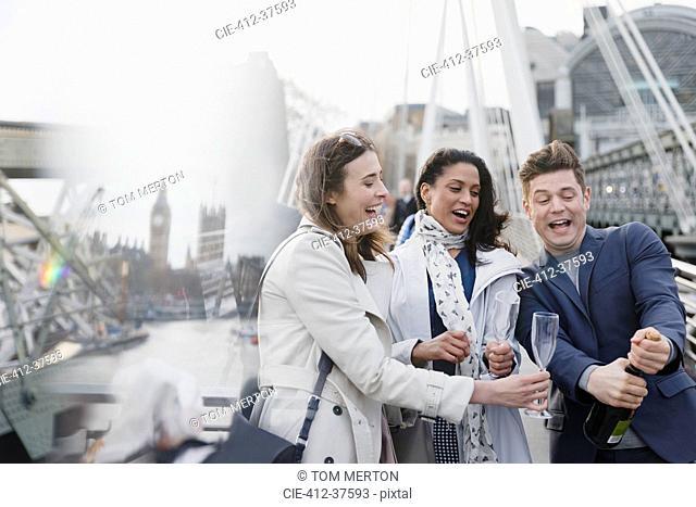 Friends popping champagne, celebrating on urban bridge, London, UK