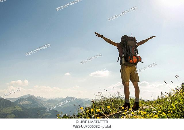 Austria, Tyrol, Tannheimer Tal, young man standing on mountain trail with arms outstretched