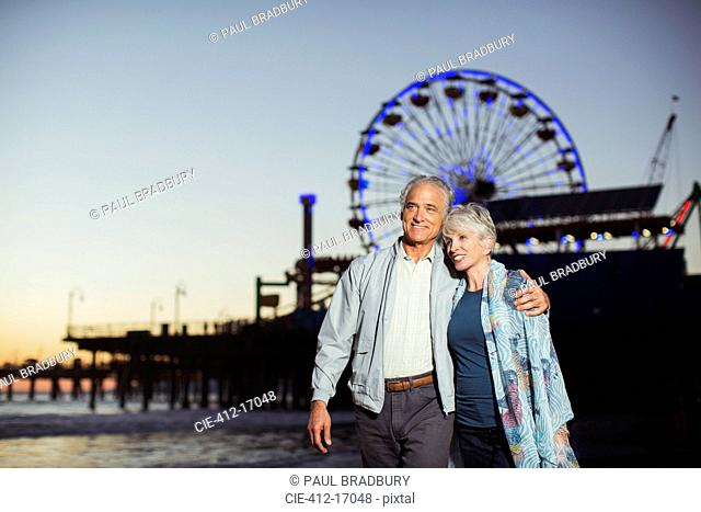 Senior couple walking on beach at night