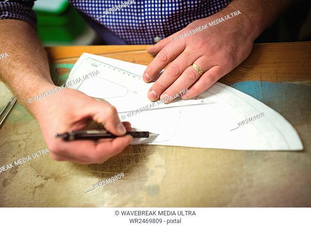 Cobbler making a design of shoe on paper in workshop
