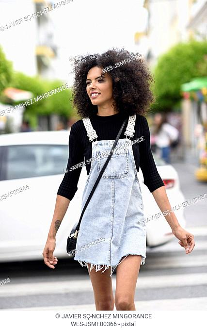 Smiling young woman crossing the street