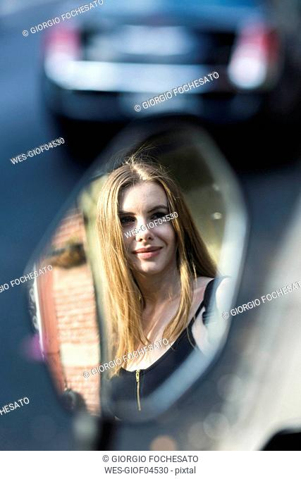 Portrait of a woman reflecting in a rear mirror