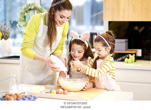 Mother and daughters baking Easter cookies in kitchen together