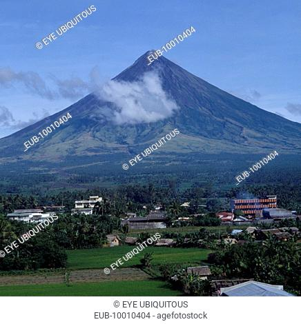 Mayon volcano with wispy cloud and village at the base