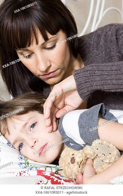 mother measuring child body temperature