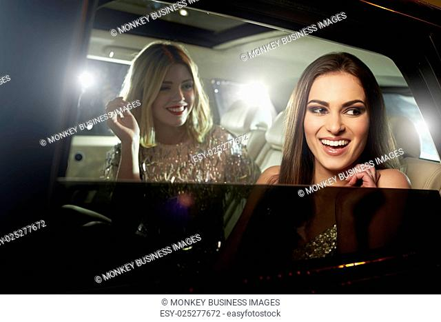 Two glamorous women laughing in the back of a limousine