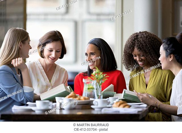 Women friends discussing book club book at restaurant table