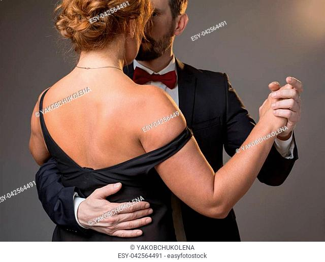 Passionate middle-aged man and woman dancing. Focus on woman back wearing black dress. Isolated