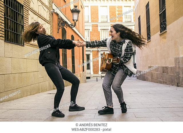 Spain, Madrid, two women dancing in a street