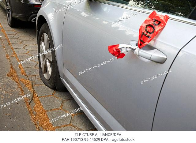 10 July 2019, Hamburg: Skoda passenger car stands with a flat tire and with the police barrier tape attached to the door handle on the parking strip of the road...