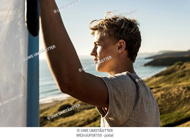 Teenage boy with surfboard looking to the sea